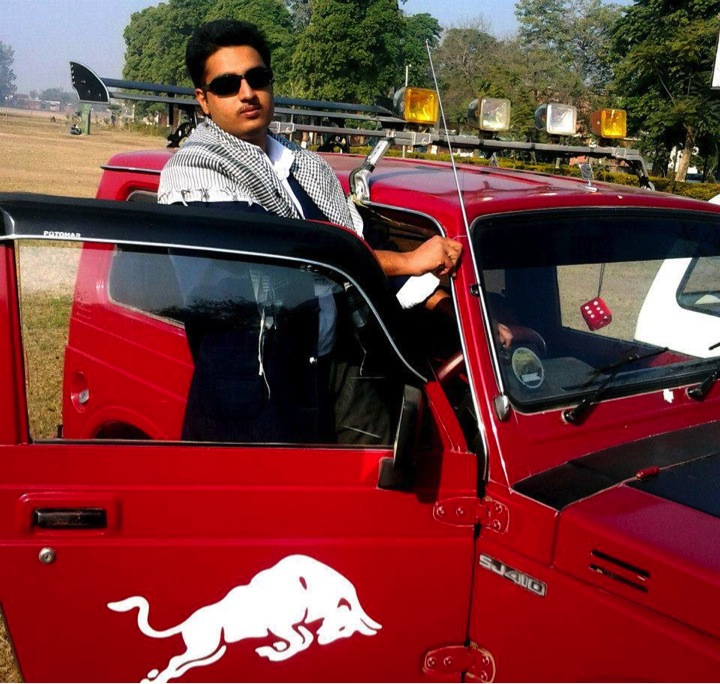 Punjabi rapper Kasim Raja posing with his vehicle.