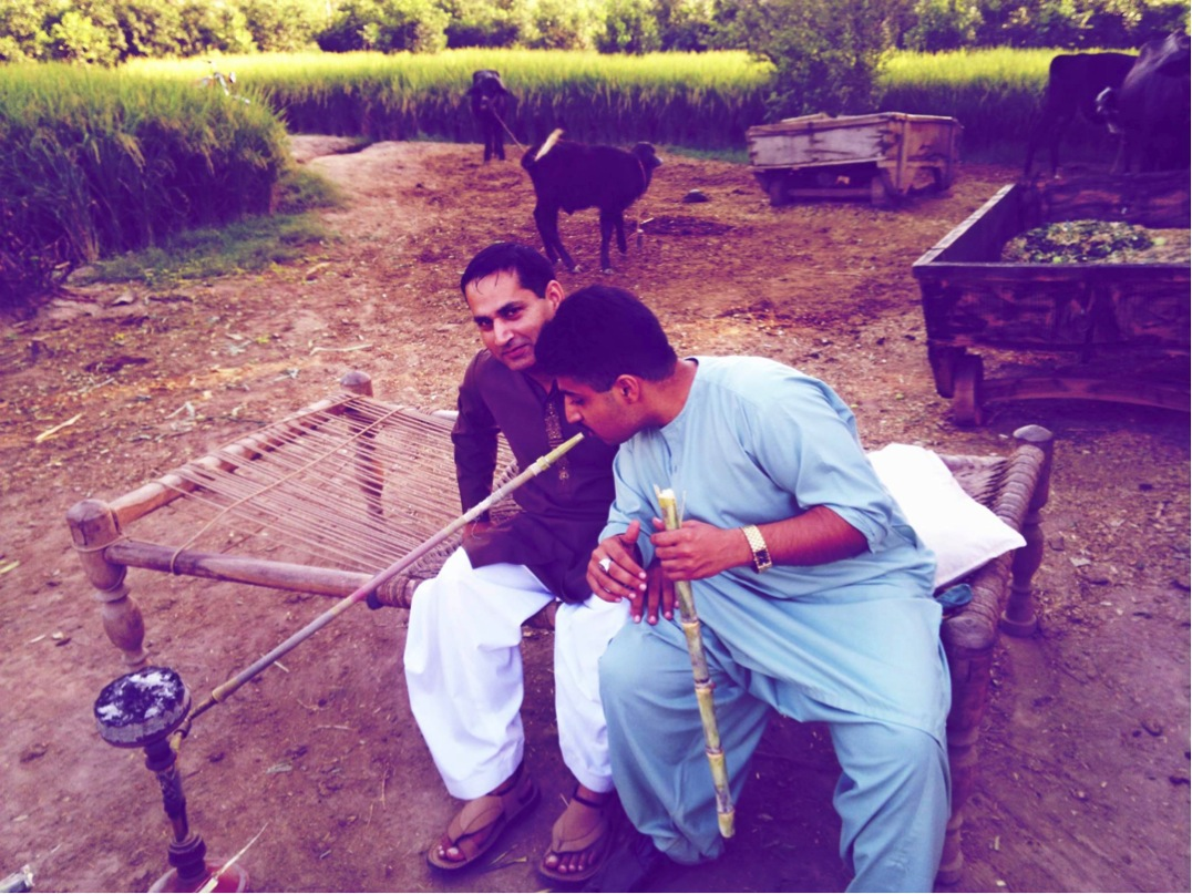 Punjabi rapper Kasim Raja (right) smoking sheehsa in his ancestral village.